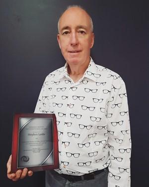 steve in glasses shirt with award